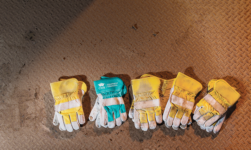 Teal CWB work glove amongst yellow ones